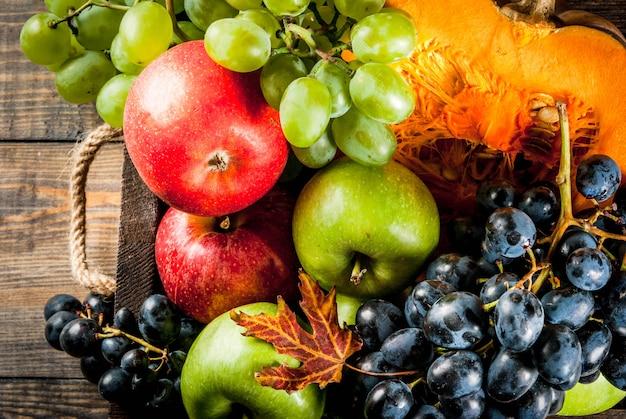 Frutas de otoño estacionales y calabaza en mesa de madera