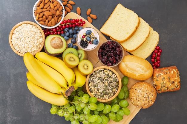 Frutas y pan, cereales integrales y nueces sobre mesa de madera