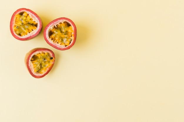Frutas de la pasión a la mitad sobre fondo beige