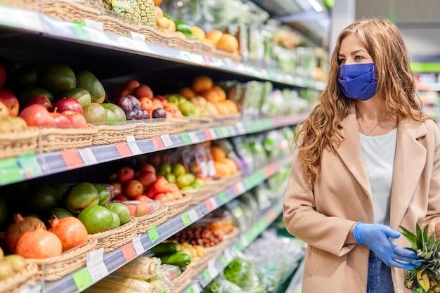 Frutas saludables con vitaminas durante la pandemia de covid-19. mujer con máscara facial compra fruta en el mercado.