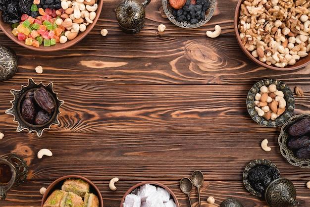 Frutas secas; fechas; lukum y baklava preparados para ramadan en mesa de madera