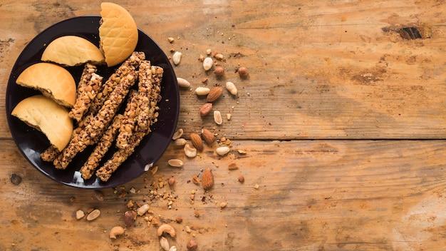 Frutas secas; galletas y barra de granola sobre fondo con textura de madera