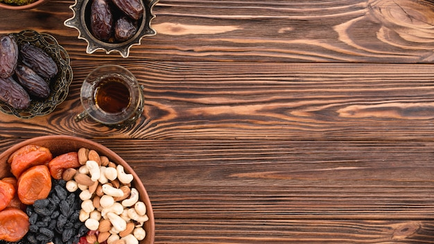 Frutas secas mixtas; nueces; fechas y té en el festival de ramadán sobre el escritorio de madera.