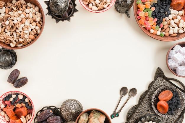 Frutas secas; nueces; fechas; lukum y baklava en un recipiente metálico sobre fondo blanco con espacio en el centro