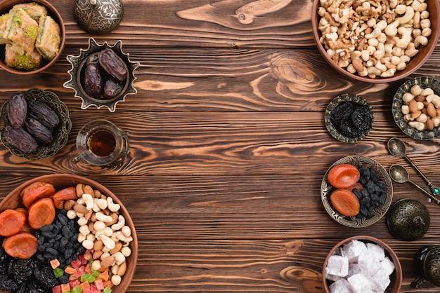 Frutas secas; nueces; fechas y lukum en cuencos de barro y metálicos en mesa de madera