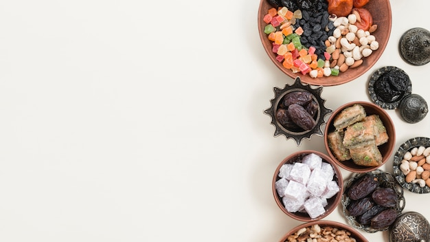 Frutas secas tradicionales turcas; nueces; lukum y baklava sobre fondo blanco