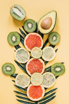 Frutas surtidas cerca de la hoja de palma