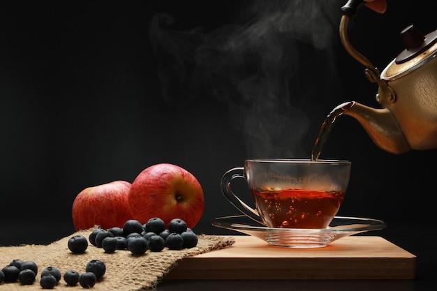 Las frutas de té caliente en un vaso con vertido de las teteras doradas con humo y arándanos