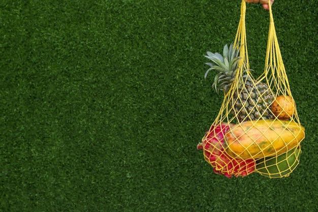 Frutas tropicales en una bolsa de textil de compras amarillo sobre un fondo verde