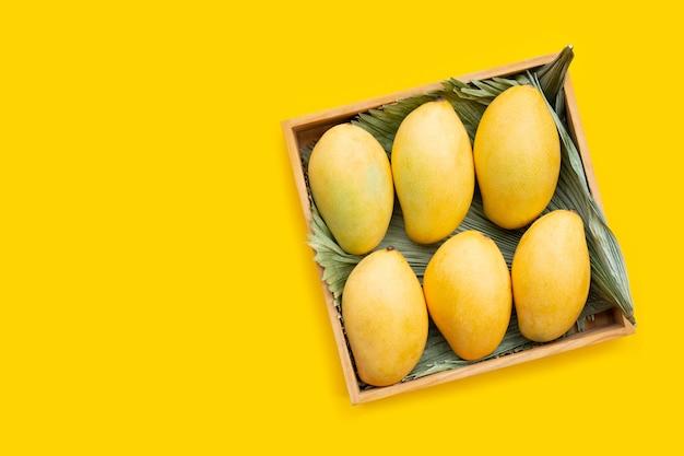 Frutas tropicales en caja de madera sobre superficie amarilla