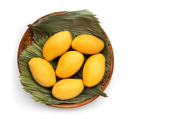 Frutas tropicales en canasta de bambú sobre superficie blanca