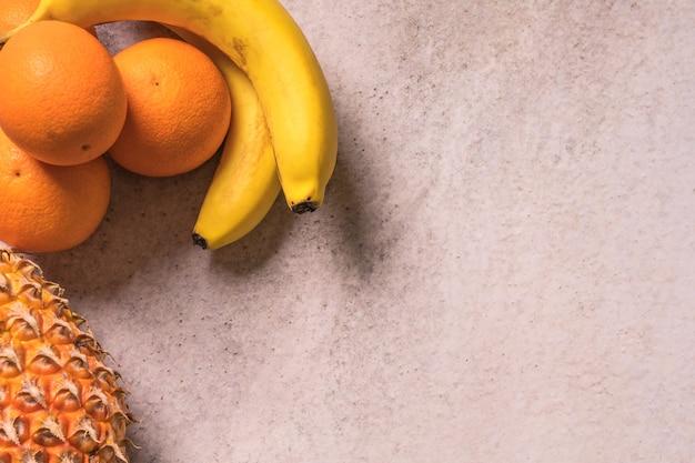Frutas tropicales y estacionales de verano. piñas, naranjas y plátanos arreglados, vidas sanas