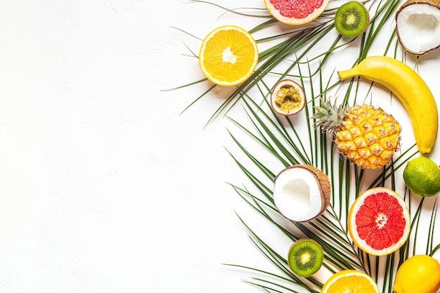 Frutas tropicales y hojas de palmera sobre un fondo blanco, vista superior.