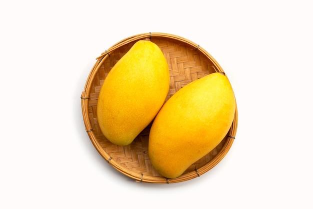 Frutas tropicales, mango en canasta de bambú sobre superficie blanca