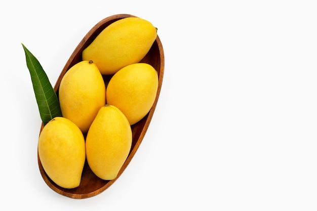 Frutas tropicales, mango en tazón de madera sobre superficie blanca
