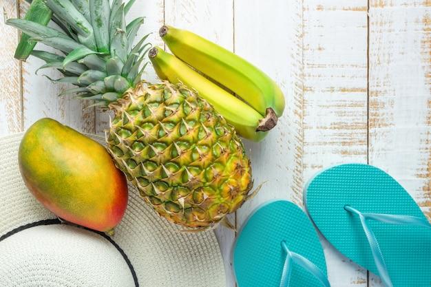 Frutas tropicales piña mango plátanos mujeres sombrero azul zapatillas