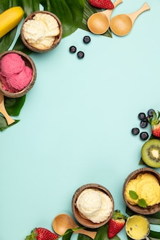 Frutas tropicales y plantas con variedad de helados en cáscaras de coco sobre fondo azul.