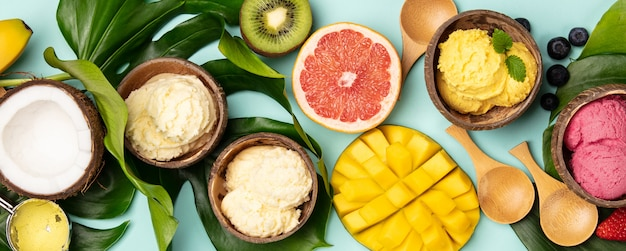Frutas tropicales y plantas con variedad de helados en cáscaras de coco.