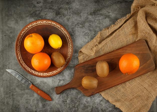 Frutas tropicales en un recipiente y sobre la plancha de madera. vista superior.