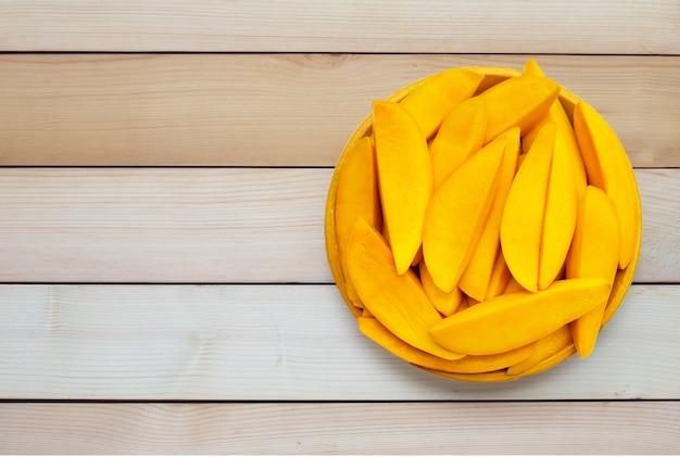 Frutas tropicales, rodajas de mango en placa amarilla sobre superficie de madera