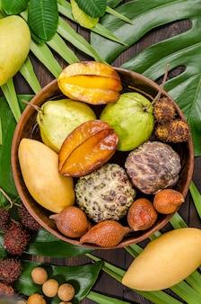 Frutas tropicales tailandesas clasificadas en un fondo rústico de madera oscuro.