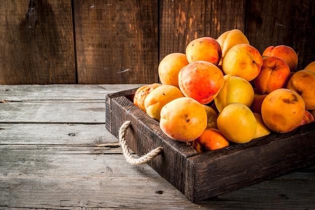 Frutas de verano albaricoques frescos crudos orgánicos granja en una caja de madera, una bandeja, sobre una vieja mesa rústica de madera.
