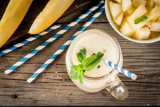 Frutas de verano, bebidas refrescantes. comida vegana. desayuno. batido de yogurt, melón amarillo orgánico crudo, semillas de lino y menta. con pajitas de rayas, en tarro de albañil, mesa rústica de madera, vista superior de copyspace
