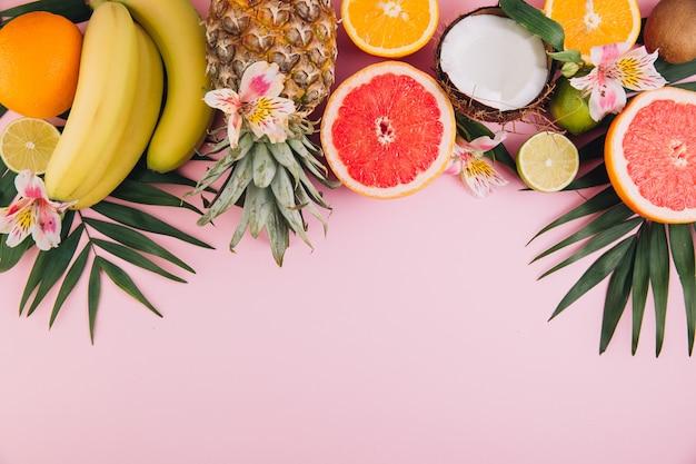 Frutas de verano. hojas de palma tropicales, piña, coco, pomelo, naranja y plátanos sobre fondo rosa.