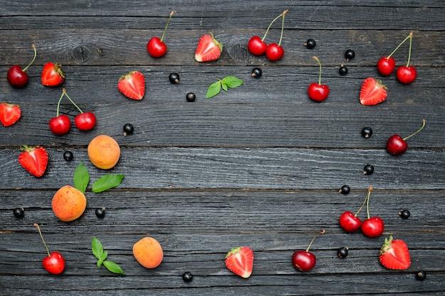 Frutas de verano sobre un fondo negro de madera. lugar para texto