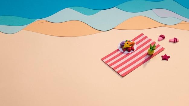 Frutas de verano en una toalla junto al mar.