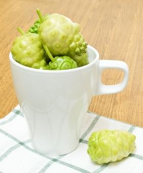 Frutas verdes de noni o morinda citrifolia en taza blanca