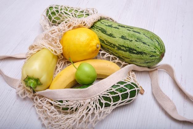 Frutas y verduras en una bolsa de malla sobre un fondo de madera