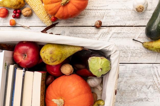 Frutas y verduras en canasta con libros