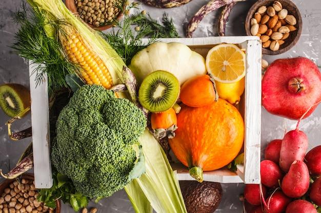 Frutas, verduras y cereales en una caja de madera, vista superior