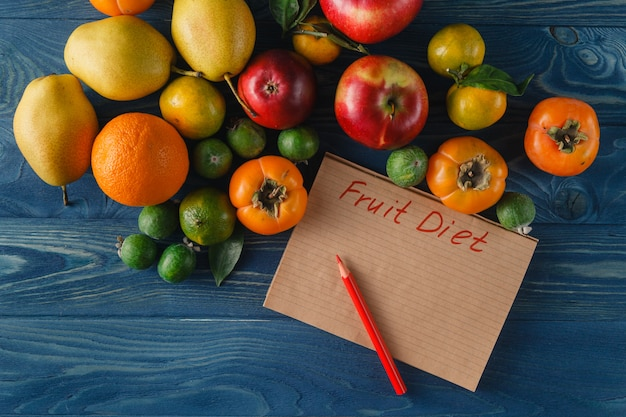 Frutas, verduras y cinta métrica en dieta sobre fondo de madera