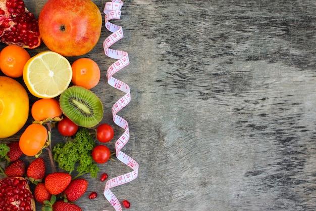 Frutas, verduras y en cinta métrica en la dieta.