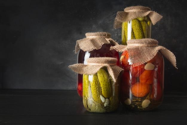 Frutas y verduras enlatadas, ciruela, pepino, tomate en frascos de vidrio sobre tabla de madera oscura.