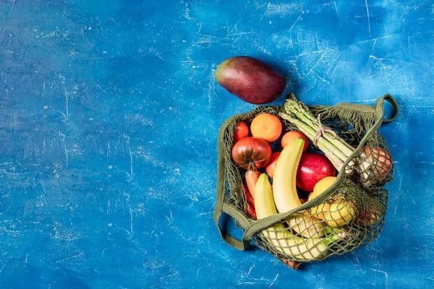 Frutas y verduras frescas en una bolsa de hilo verde sobre una mesa de color azul claro. sin plástico, solo materiales naturales y productos naturales.