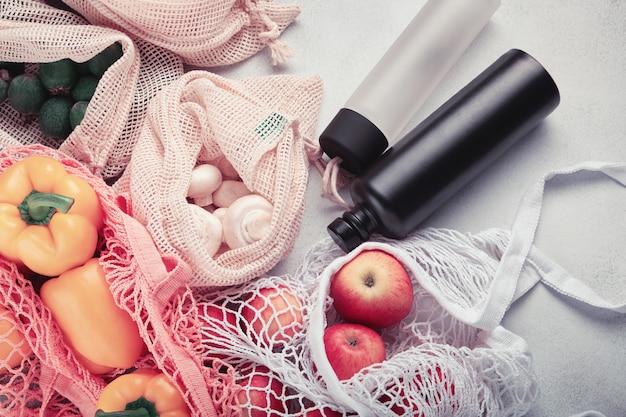 Frutas y verduras frescas en bolsas ecológicas, botellas de agua reutilizables. compras sin desperdicio