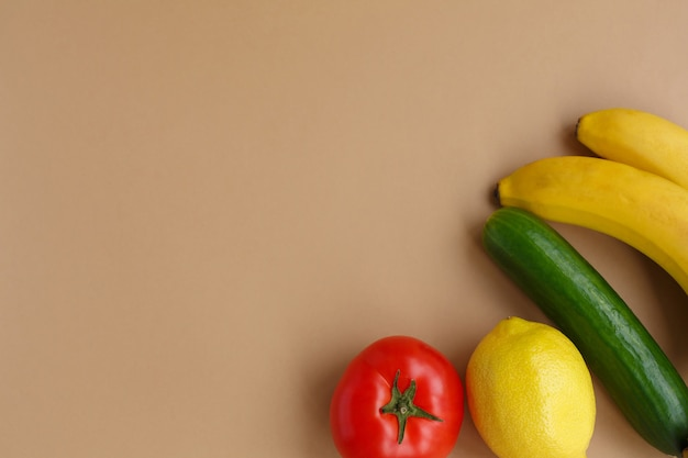 Frutas y verduras frescas. dieta y nutrición saludables. limón y plátano, tomate y pepino sobre un fondo sólido claro