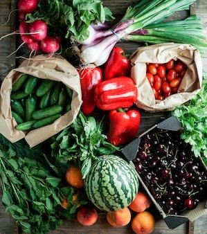 Frutas y verduras frescas y maduras en embalaje de papel ecológico, cereza, pimiento, sandía, tomates cerry, hierbas