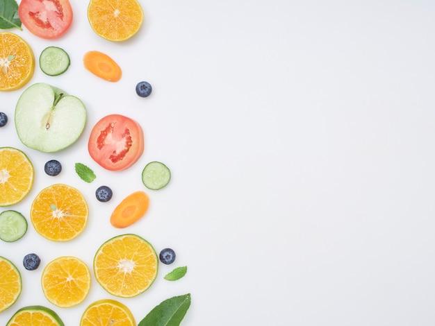 Frutas y verduras frescas en rodajas sobre fondo blanco.