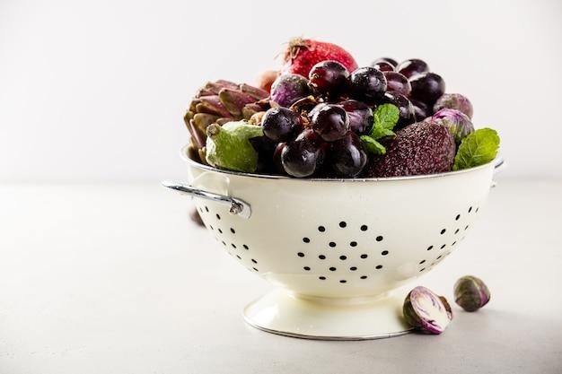 Frutas y verduras moradas en colador
