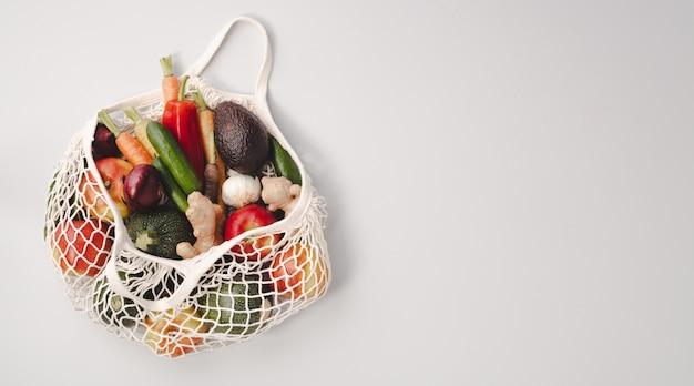 Frutas y verduras orgánicas frescas en bolsa textil de malla