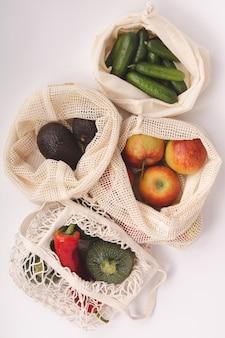 Frutas y verduras orgánicas frescas en bolsas ecológicas de algodón.