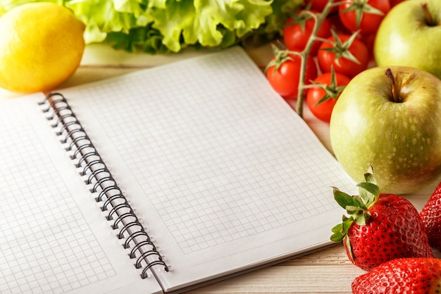 Frutas y verduras orgánicas frescas, cuaderno en blanco abierto y pluma en la mesa de madera.