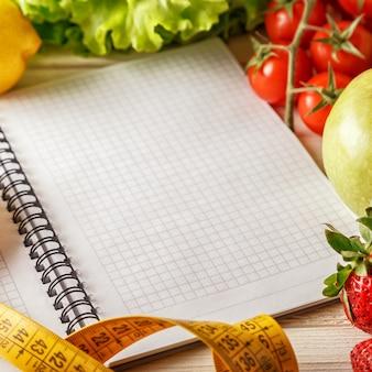 Frutas y verduras orgánicas frescas, cuaderno y pluma en blanco abiertos