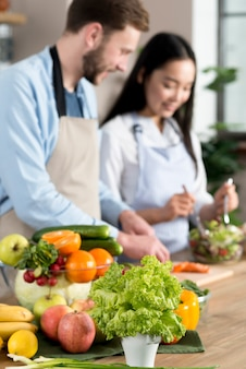 Frutas y verduras saludables frente a una pareja desenfocada que prepara la comida en la cocina