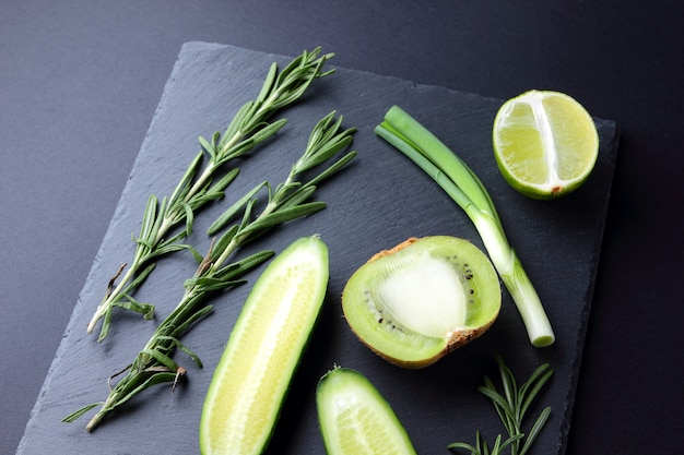 Frutas y verduras verdes en tablero de pizarra oscura. concepto de productos verdes naturales. aguacate, kiwi, limón y manzana sobre fondo oscuro. romero, eneldo y cebollino sobre tabla de piedra