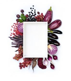Frutas y verduras violetas crudas alrededor del plato